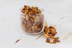 granola i glasburk, sked, vit träbakgrund foto