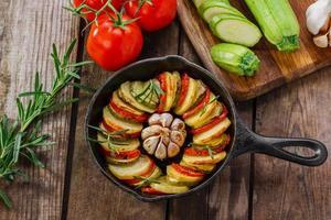 bakade potatis med zucchini och tomater foto