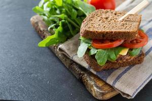 grönsakssmörgås med zucchini hamburgare, ost, ruccola och tomater foto