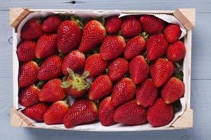 trälåda med färska jordgubbar foto