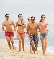 aktiva vänner springer på sandstranden foto