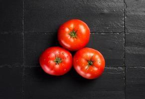färska och hälsa tomater över svart skiffer foto