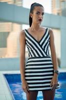 vacker brunett i en randig klänning foto