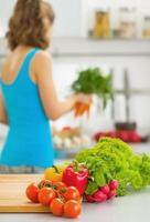 grönsaker på skärbräda och kvinna i bakgrunden. närbild foto