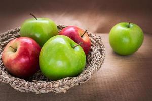 grönt äpple och rött äpple i korg, stilleben foto