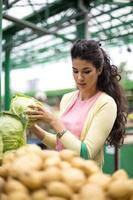 kvinna som köper grönsaker på marknaden foto