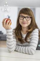 porträtt av tonårsflickan som håller äpplet när man sitter vid bordet foto