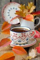kopp te på bordet med höstlöv foto