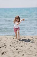 litet kvinnligt barn porträtt på stranden foto