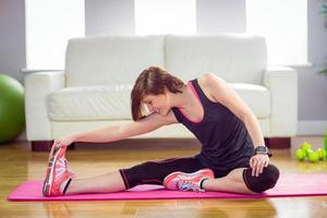 fit kvinna som sträcker sig på träningsmatta foto