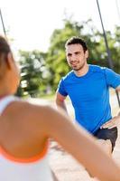 atletisk man och kvinna som sträcker sig utomhus på en varm sommar foto