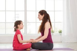 ung mamma och dotter som gör yogaövning foto
