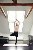 ung kvinna som utövar yoga i vardagsrummet foto