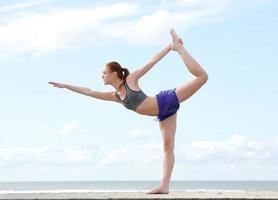 ung kvinna balanserar på ett ben i yogaposition foto