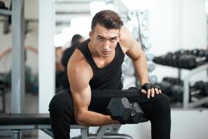 man gör övningar hantel bicep muskler foto