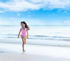 liten asiatisk tjej springa på stranden foto