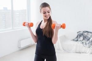 aktiv sportig atletisk kvinna med hantlar som pumpar upp musklerna biceps foto