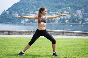 ung attraktiv kvinna som gör övningar utomhus foto