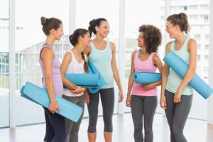 passar leende unga kvinnor med träningsmattor foto