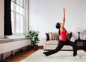 ung kvinna som tränar i ett vardagsrum foto