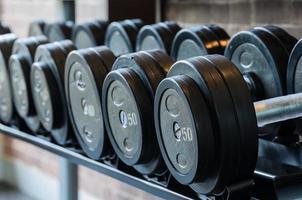 skivstångsvikter som är organiserade på gymmet foto