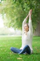 ung kvinna mediterar och yoga i en park foto