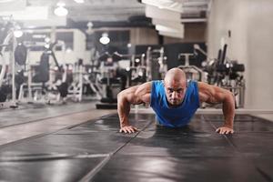 bodybuilder träna och göra push upsat gymmet medan foto