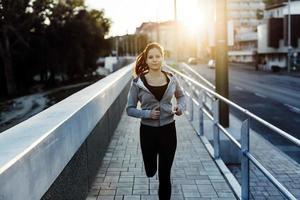 vacker kvinnlig jogging i staden foto