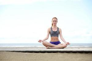 vacker ung kvinna som sitter utomhus i yogaställning foto