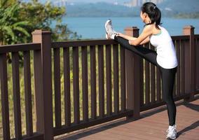 sportkvinna som sträcker benen innan du springer foto