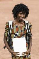 afrikansk svart kvinna med träningsbok och säck foto