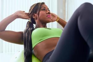 hem fitness svart kvinna träning abs med schweizisk boll foto