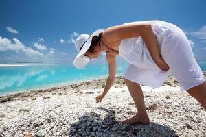 kaukasisk kvinna som samlar snäckskal på stranden foto