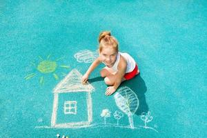 trevlig kaukasisk liten flicka rita krita hus bild foto