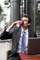 ung kaukasisk affärsman som använder sin bärbara dator i café och dricker foto