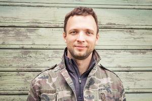 ung kaukasisk man i utomhusporträtt för kamouflage foto