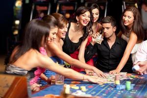 glada kaukasiska vänner som spelar roulette i kasinot foto