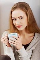 vacker avslappnad kaukasisk kvinna som sitter med varm dryck. foto