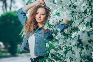 vacker ung kaukasisk flicka med lockigt hår utomhus