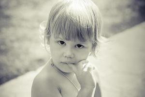 porträtt av söta tänkande kaukasiska blonda baby gir foto