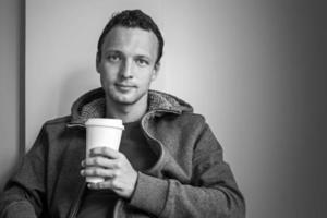 porträtt av ung kaukasisk man som sitter på café foto