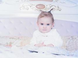 liten kaukasisk barnflicka som sitter på sängen hemma