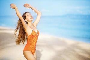 ung vacker kaukasisk kvinna med långt hår på en strand foto