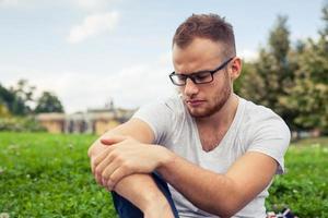 porträtt av skäggig ung man. ledsen kaukasisk man i parken. foto