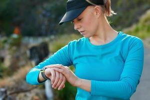 fit, kaukasisk kvinna som kontrollerar tiden under en träningskörning foto