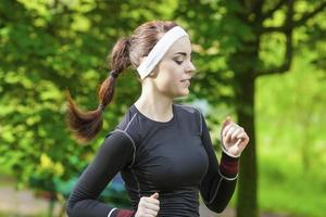 porträtt av leende kaukasiska sportkvinna som har sin regelbundna träning utomhus. foto