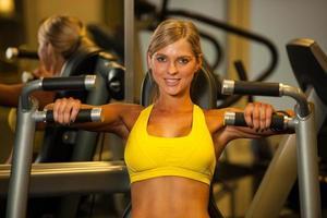 vacker kaukasisk kvinna som arbetar ut sina armar i fitness foto