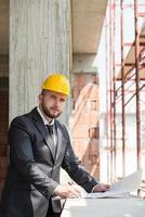 kaukasiska manliga byggnadschef med ritning foto