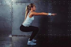atletisk ung kvinna fitness modell värmer upp gör squats träning foto