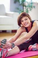 fit kvinna tittar på kameran och sträcker sig på träningsmatta foto